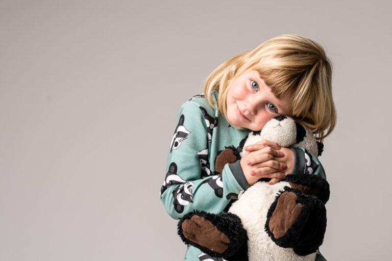 foto in de studio van een kindje dat een beertje vasthoudt