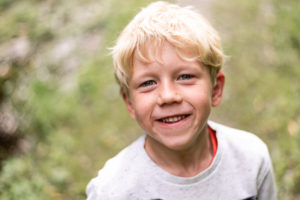 portret van een blond lachend kindje in het bos